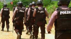 Armed policemen walk in Indonesian jungle - stock footage
