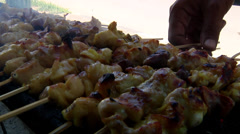 Turning over chicken satay on grill Stock Footage