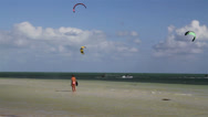 Stock Video Footage of People engage in the fast moving sport kite boarding  along a sunny coast.