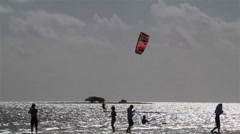 People engage in kite boarding  along a sunny coast. Stock Footage