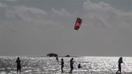 Stock Video Footage of People engage in kite boarding  along a sunny coast.