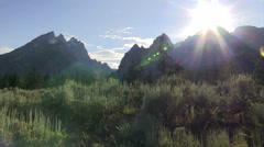 Pan across the sun peeking above the Grand Tetons mountains. - stock footage