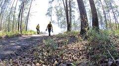 Low angle of a fire crew member lighting a prescribed fire with a drip torch in Stock Footage