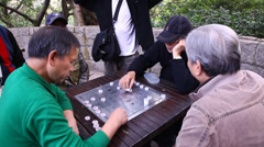 Men play Chinese board game in the park Stock Footage