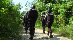 Armed police search jungle Stock Footage