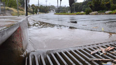 Water flowing down a street gutter into a storm drain after heavy rain in Stock Footage