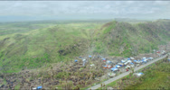 Aerial of destroyed community near hills with broken trees Stock Footage