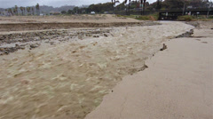 Panning shot of Sanjon Creek washing beach sand into the ocean after heavy rain Stock Footage