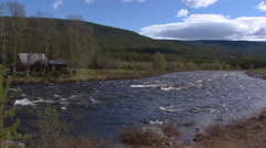 RONDANE, NORWAY: Atnedal valley, river in spring, cabin on lakeside Stock Footage