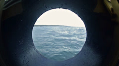 View through a ship's porthole of guests departing on an inflatable raft in the Stock Footage