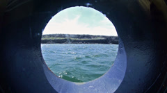 View through a ship's porthole of snorkelers departing on an inflatable raft in Stock Footage