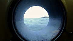 View through a ship's porthole of waves splashing in the Galapagos Islands Stock Footage