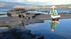 Young photographer enjoying two Galapagos Sea Lion pups playing at Puerto Egas Stock Footage
