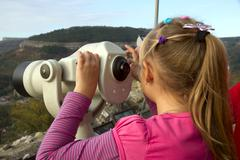 Stock Photo of girl looks into the distance through a telescope