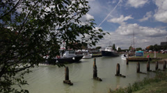Boats passing along a busy river, blue skys - harbour - Rye, East Sussex Stock Footage