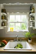 kitchen window, with shelves and a traditional sink, tap and running water fo - stock photo