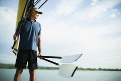 a middle-aged man carrying oars and a rowing shell on his shoulder. - stock photo