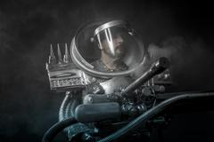 strong astronaut on a black background with huge weapon. - stock photo