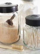 Sturdy glass storage jars for body scrub granules and for cottonwool and othe Stock Photos