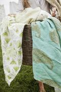 A basket overflowing with household linens. washing basket. Stock Photos