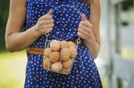 Stock Photo of a woman holding a basket of hen's eggs gathered from the chickens on a farm.