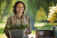 Stock Photo of a young woman with a large bucket of salad vegetables leaves freshly picked.