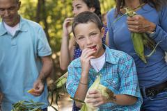 a group of young people eating raw fresh vegetables, sweet corn cobs, just af - stock photo