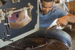 Machinery at a coffee bean processing shed heating and  roasting coffee beans Stock Photos