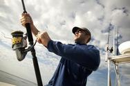 A man on a boat holding a fishing rod. Stock Photos