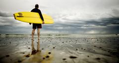 A middle aged man surfing in new england on rockport beach. Stock Photos