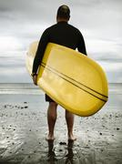 a middle aged man surfing in new england on rockport beach. - stock photo