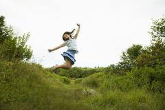 A young girl, leaping for joy, kicking up her heels in the air. Stock Photos