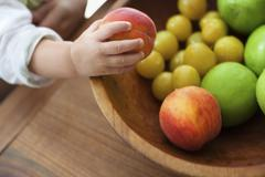 a small child, a one year old girl, grasping fruit from a bowl. - stock photo