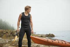 A man in a wetsuit drawing his kayak onto the shore, in misty weather.  new y Stock Photos