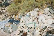 Stock Photo of a heap of garbage and discarded items. rubbish, paper and a children's doll.