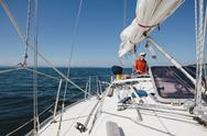 Stock Photo of middle aged man steering sailboat on puget sound, washington, usa