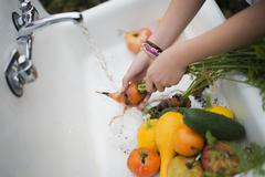 Organic farming. a young girl washing vegetables under a tap. Stock Photos