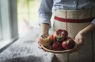 Stock Photo of a person holding a bowl of organic red skinned apples.