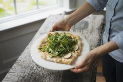 A person holding a plate with fresh salad and ingredients on baked bread. Stock Photos
