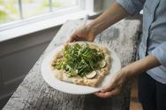 Stock Photo of a person holding a plate with fresh salad and ingredients on baked bread.