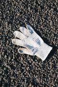 Discarded white glove on the ground. Stock Photos