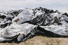 Black and white discarded plastic bags, used for covering bales of hay Stock Photos