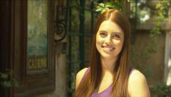 Beautiful girl not smiling, then smiling at a french provincial villa - stock footage