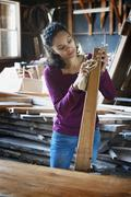 Stock Photo of a woman working with reclaimed timber in a woodwork workshop.