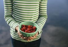 nine year old girl holding bowl of organic raspberries - stock photo