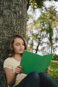 nine year old girl sitting beneath tree, reading book - stock photo