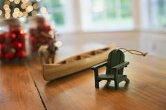 christmas decorations on a table. a handmade wooden canoe and a small chair. - stock photo