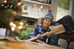a boy by a christmas tree unwrapping a gift, a wooden oar. - stock photo