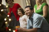 Stock Photo of a christmas gathering, adults and children in a room around a christmas tree,