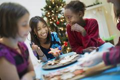 A group of children around a table, decorating organic christmas cookies. Stock Photos